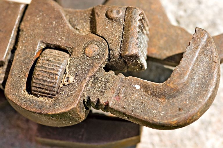 Close-up of slightly rusted, dirty pipe wrench